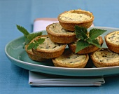 Small sour cream & nettle quiches, in a pile on a platter