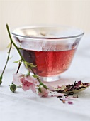 A bowl of rose tea with dried and fresh flowers