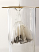 Several tea bags hanging on wooden sticks in a glass beaker