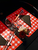 Table laid for two with roses in a vase
