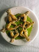 Deep-fried frogs' legs on herb sauce