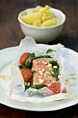 Salmon cooked in paper with garlic, almonds, spinach, tomatoes