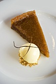 A piece of treacle tart with vanilla ice cream (UK)