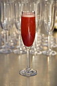 A glass of sparkling wine with strawberry puree