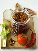 Tomato relish in a preserving jar with ingredients