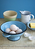 Eggs in a colander with butter and a measuring jug