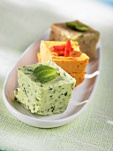 Three cubes of herb and spice butter in a small dish