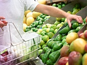 Woman with shopping basket in front of fruit counter
