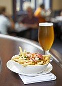 Lobster poutine with glass of beer in restaurant (Canada)