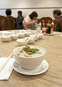 A bowl of congee in a restaurant (rice porridge, China)