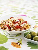Spaghetti with ham, peppers, pumpkin seeds and olives