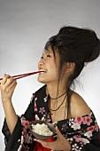 Eine Japanerin isst lachend Reis