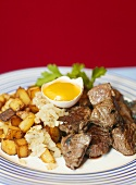 Cubes of beef steak with fried potatoes and an egg yolk