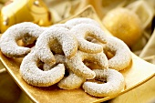 Vanilla crescents sprinkled with icing sugar on gold plate