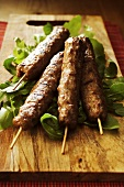 Grilled kebabs with rocket on a wooden board