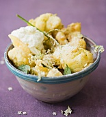 Elderflower fritters with icing sugar in a ceramic bowl