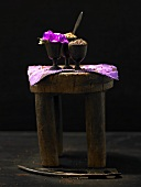 Spices and flowers in goblets on a wooden stool