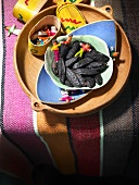 Tonka beans and toys in a wooden dish