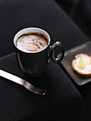 A cup of cappuccino with bread and honey