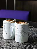 Two mugs of espresso with whisky, whipped cream & cinnamon