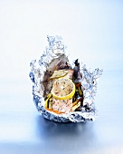 Salmon with herbs and vegetables cooked in aluminium foil