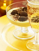 Chocolate truffles in almond cream, glass of sparkling wine