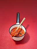 Tomato sauce in a small pan with a wooden spoon