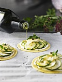 Drizzling courgette puff pastry tarts with olive oil