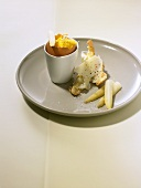 Orange scrambled egg in eggcup with asparagus & cheese baguette