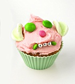 Cupcake with buttercream and amusing face made from sweets