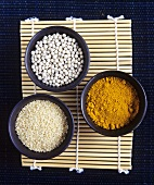 Curry powder, sesame seeds and mung beans in small bowls