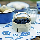 Fresh blueberries in a small woodchip basket