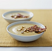 Two plates of peanut soup with fried bacon