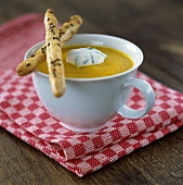 A cup of carrot soup with savoury puff pastry straws