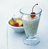 Pineapple and coconut cocktail on ice with cocktail cherry