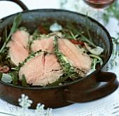 Slices of roast beef with herbs on rocket salad