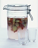 Bottled rhubarb in preserving jar, two glasses