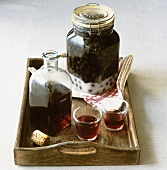 Sloe gin in carafe, glasses and preserving jar