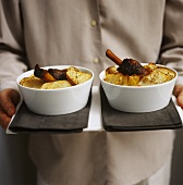 Man carrying tray with two dishes of lamb stew with potatoes