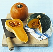 Various pumpkins & squashes on wooden board with cleaver