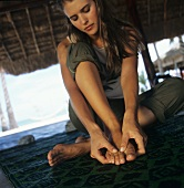 Young woman massaging her feet