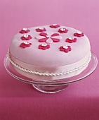 Fruit cake with pink fondant icing and sugar flowers