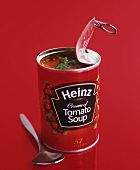 An opened tin of 'Heinz Tomato Soup' with pesto and spoon