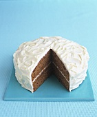 Carrot cake with cream cheese icing, a piece removed