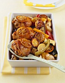 Chicken legs with lemon and vegetables in a baking dish