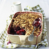 Apple and blackberry crumble in a baking dish, jug of cream