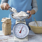 Woman weighing flour on scales