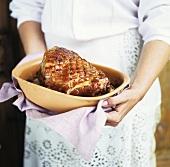 Woman holding roast ham in terracotta pot