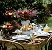 Sommerlich gedeckter Tisch mit Blumen und Früchten im Freien