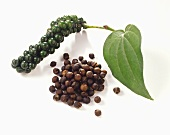 Bunch of green peppercorns with leaf and loose peppercorns